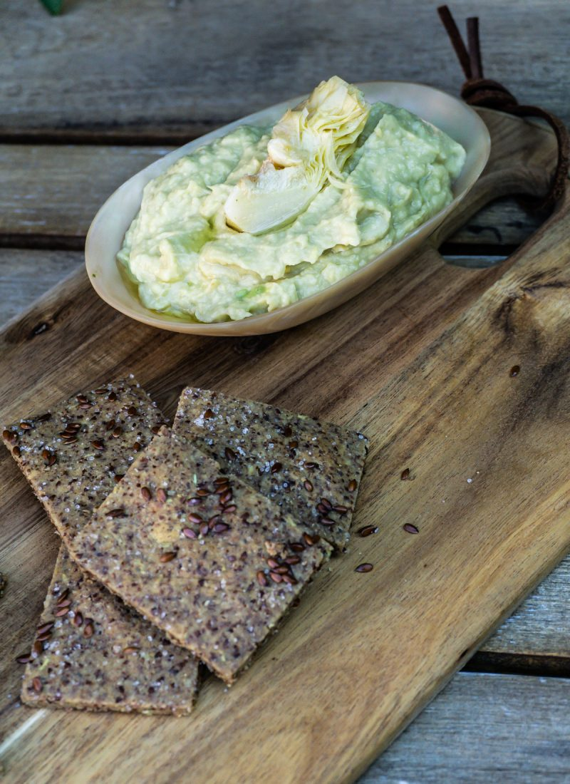 Delicious Artichoke Dip and Easy Peasy Flax Crackers on a wooden board