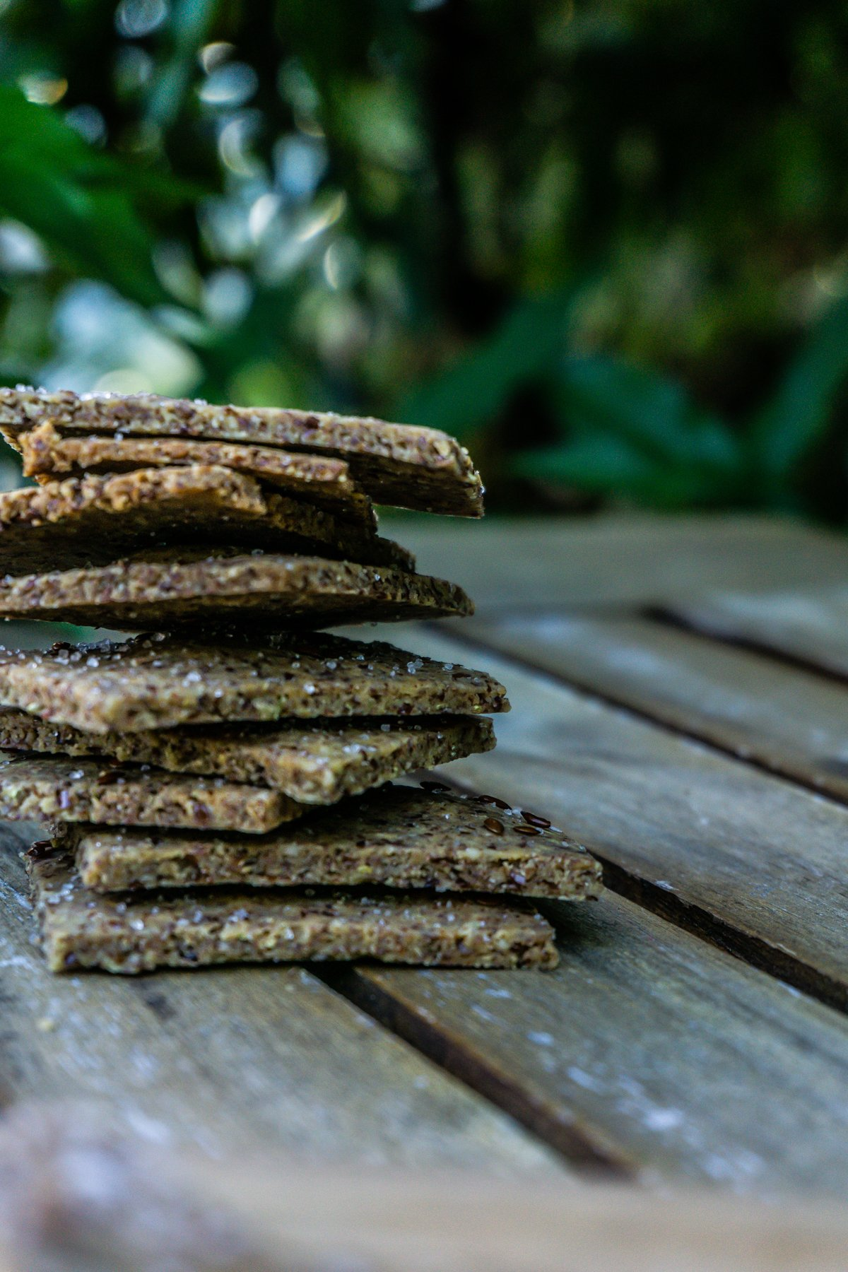 Stacked Easy Peasy Flax Crackers on a wooden table with greenery in the background