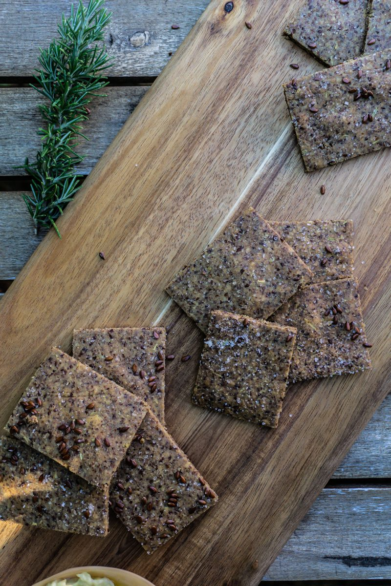 Easy Peasy Flax Crackers on a wooden board with rosemary in the background