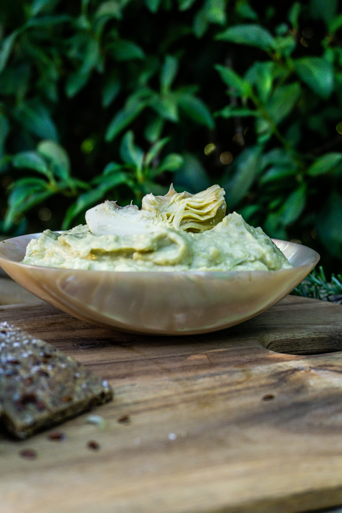 Delicious Artichoke Dip in a bowl with greenery in the background