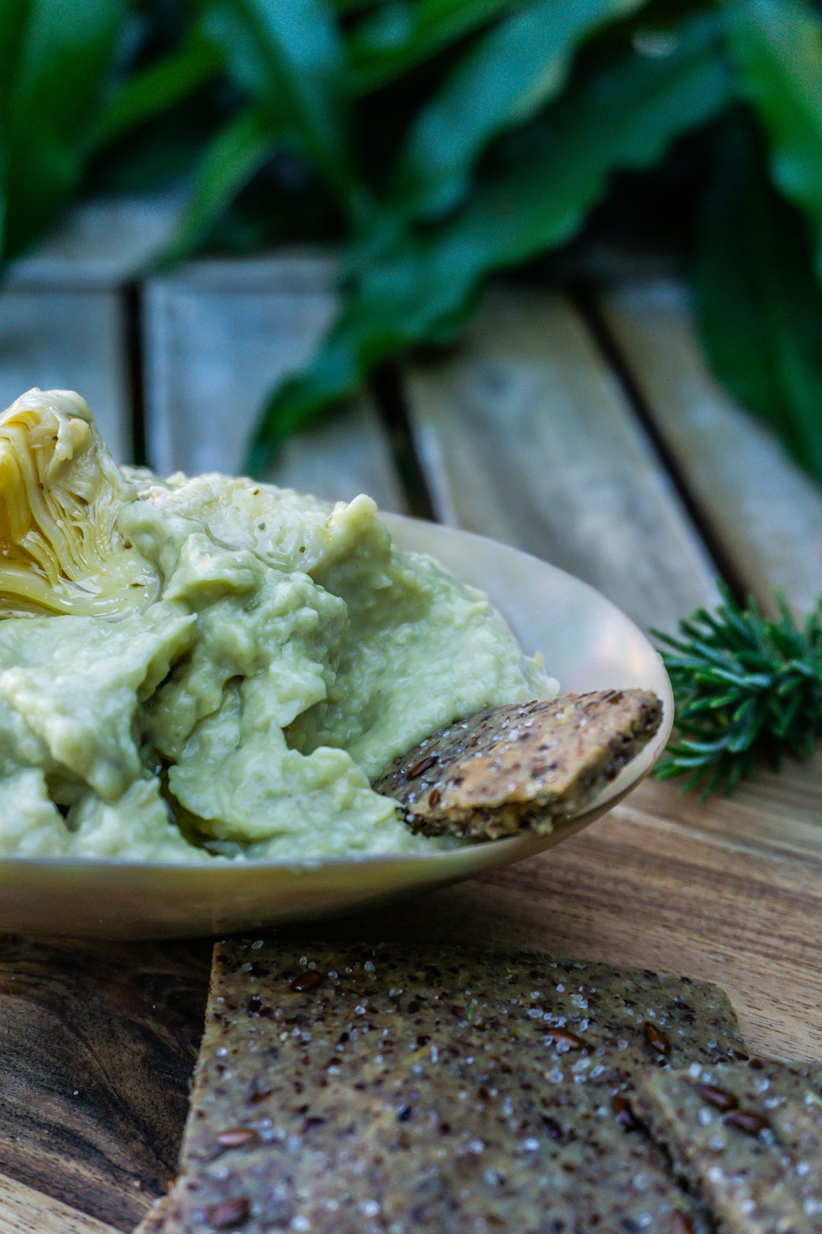 Easy Peasy Flax Cracker being dipped into delicious Artichoke Dip