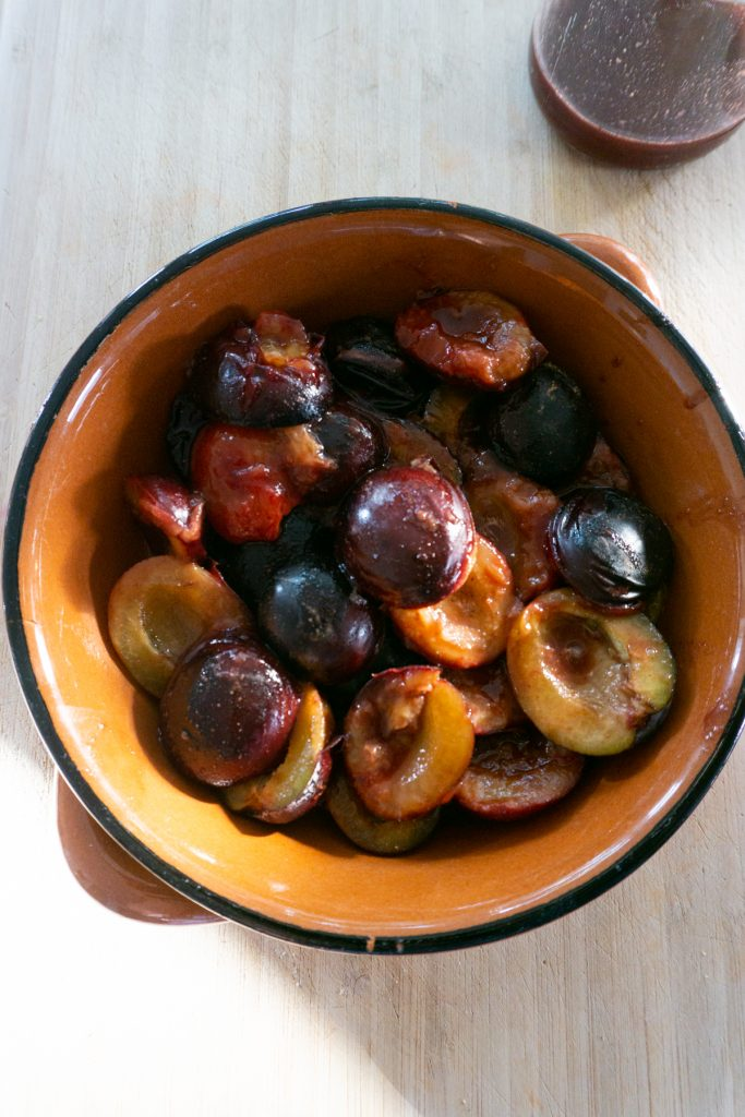 Slightly heated plums in a round baking dish