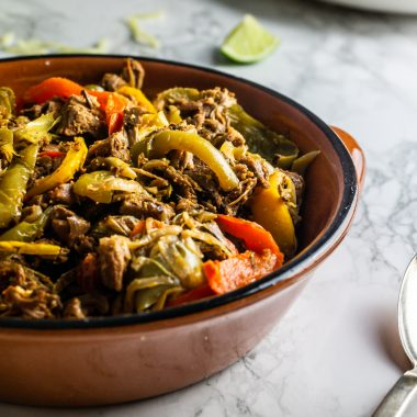 Mexican-Inspired Jackfruit Fajitas in a ramekin bowl with a spoon on a marble background shot up close