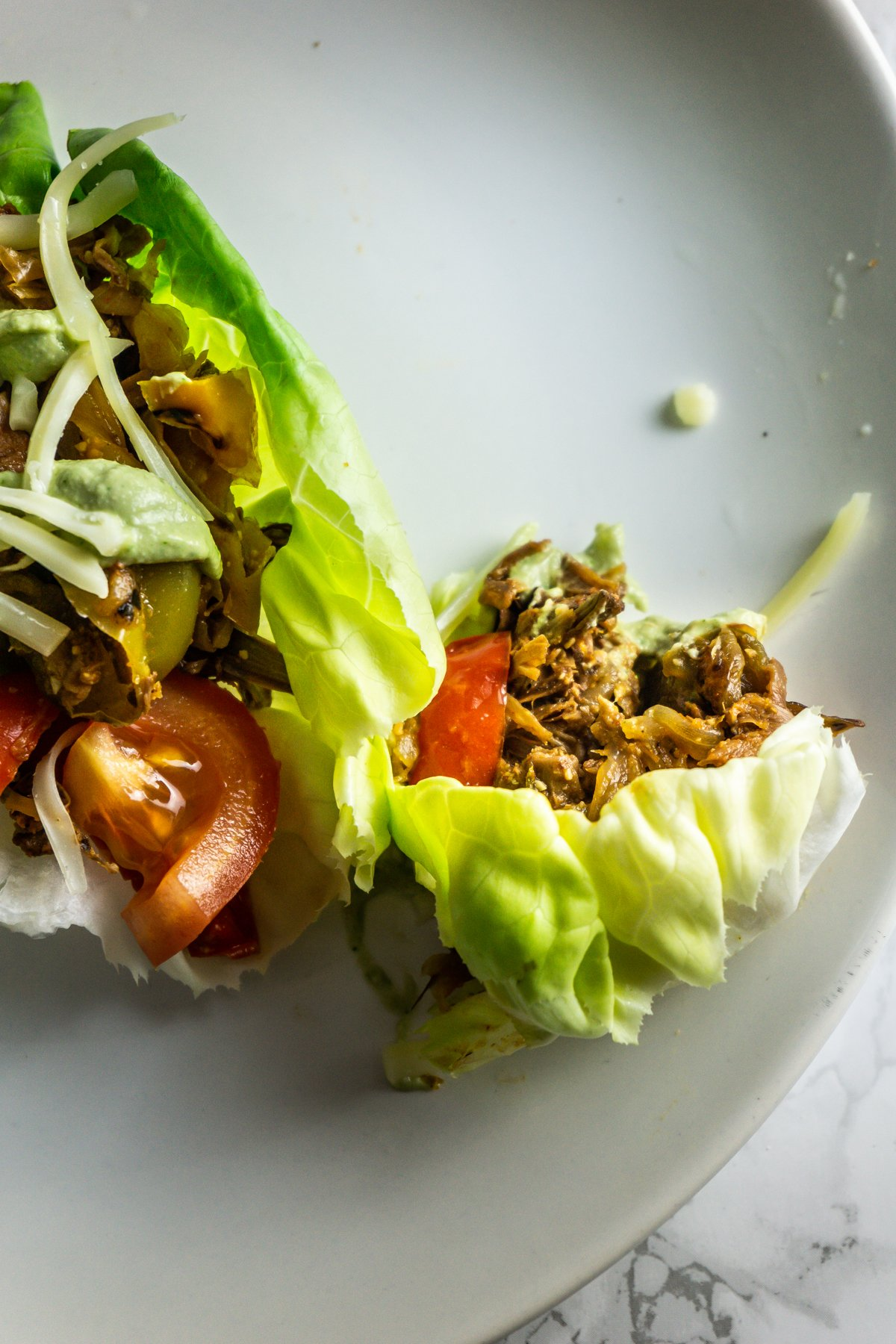 Mexican-Inspired Jackfruit Fajitas in lettuce wraps on a plate bit into