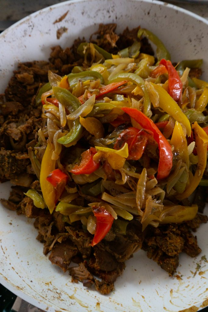Adding cooked onions and bell peppers to jackfruit covered in spices
