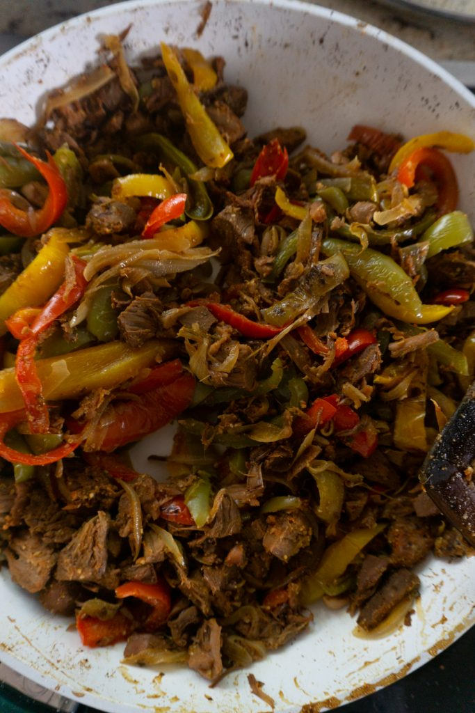 Mixing cooked onions and bell peppers to jackfruit covered in spices