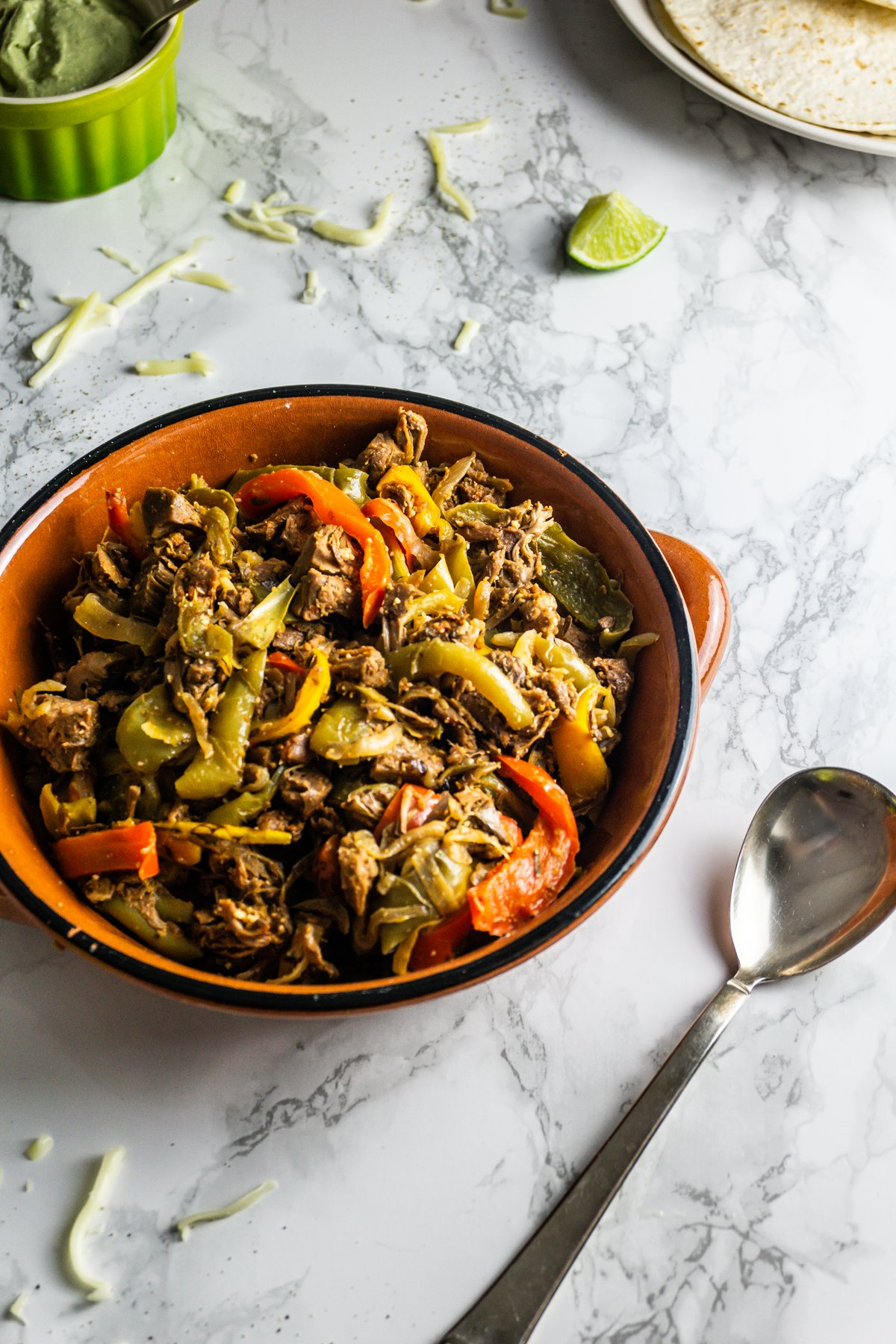 Mexican-Inspired Jackfruit Fajitas in a ramekin bowl with a spoon on a marble background
