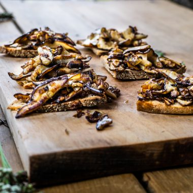 Rustic Mushroom Bruschetta on a wooden chopping board and table photographed from a three-quarter angle with greenery in the background