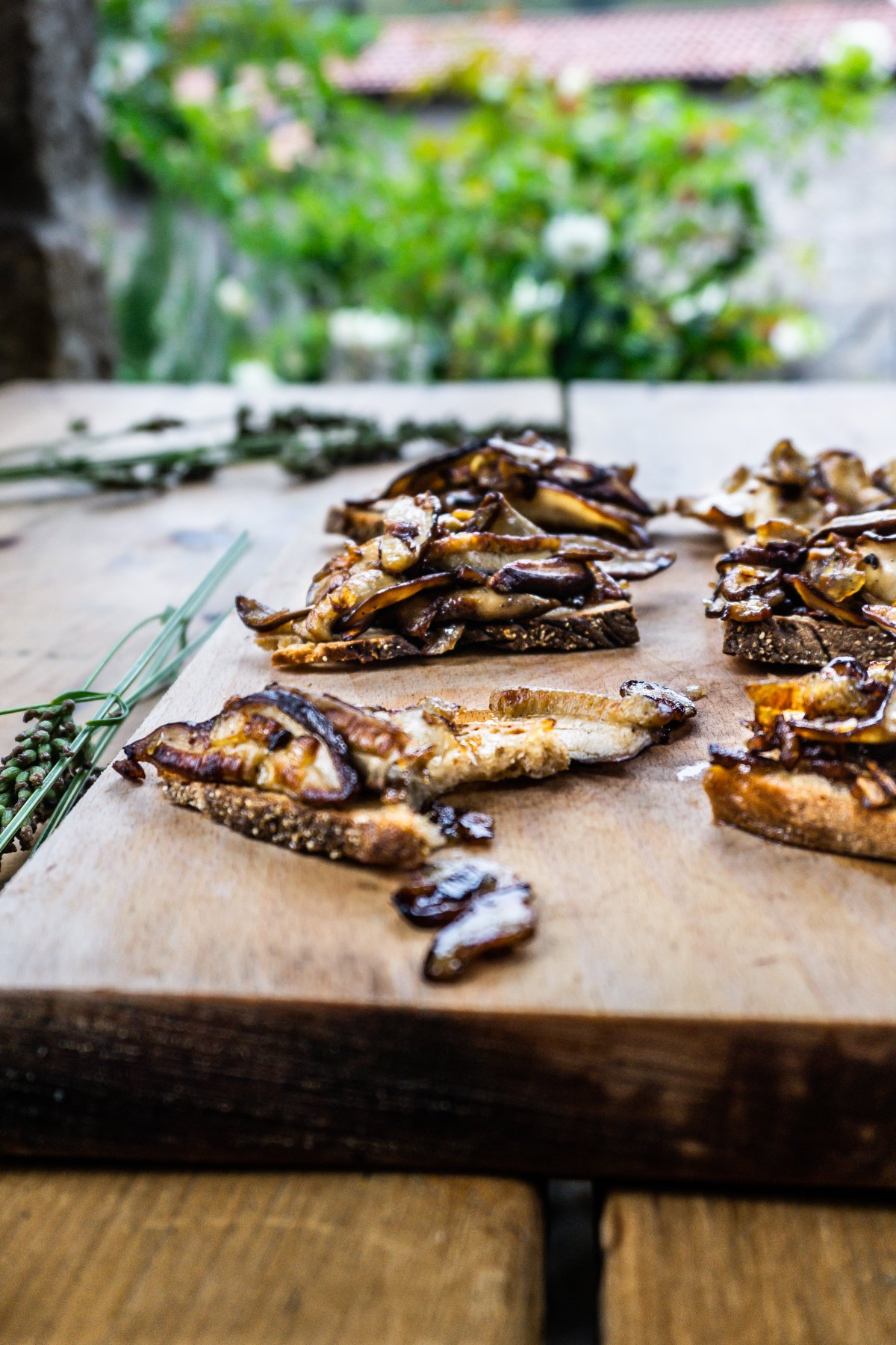 Rustic Mushroom Bruschetta on a wooden chopping board and table with one piece being bitten off and in focus