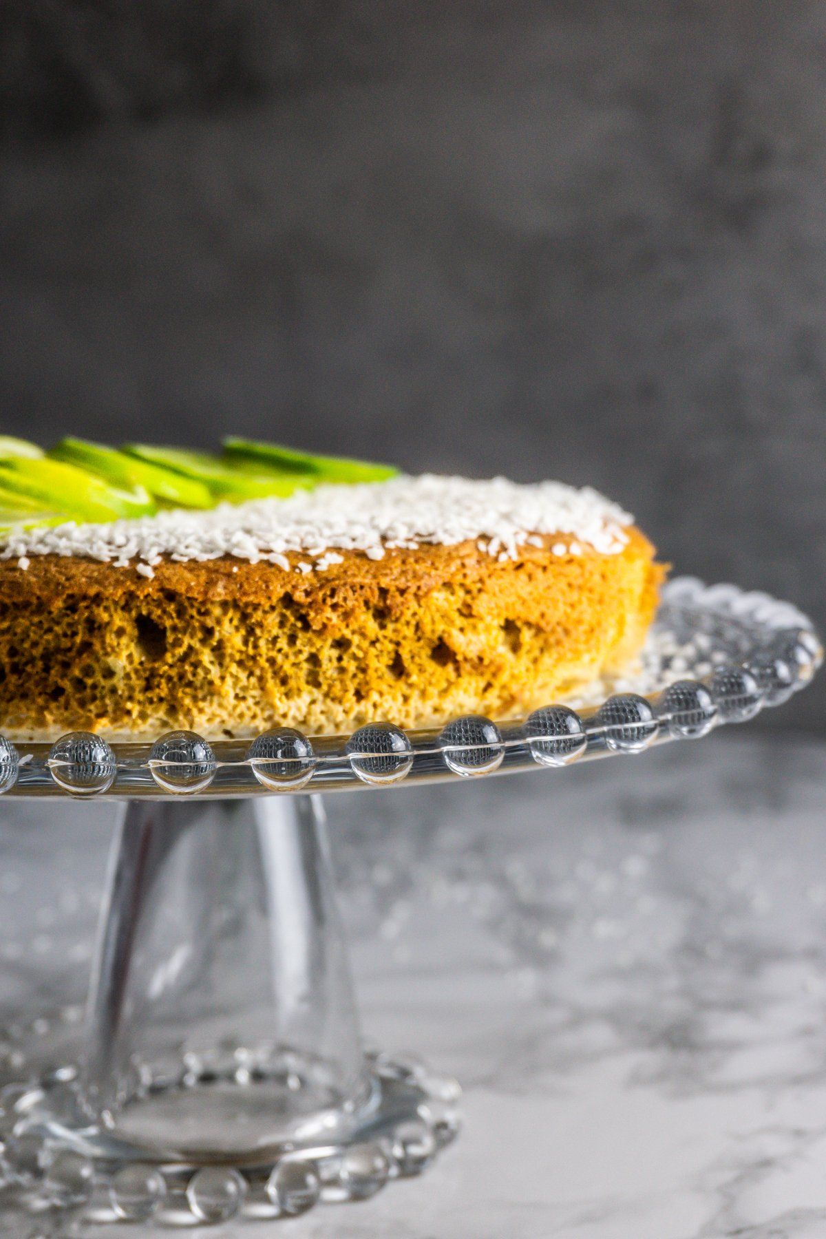 Very Coconutty and Lime Naked Cake on a glass cake stand shot from the side