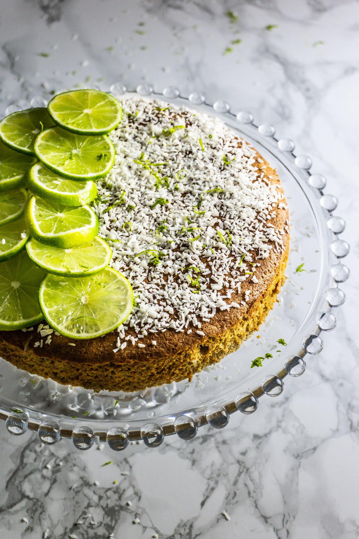 Very Coconutty and Lime Naked Cake on a glass cake stand shot at a three quarter angle