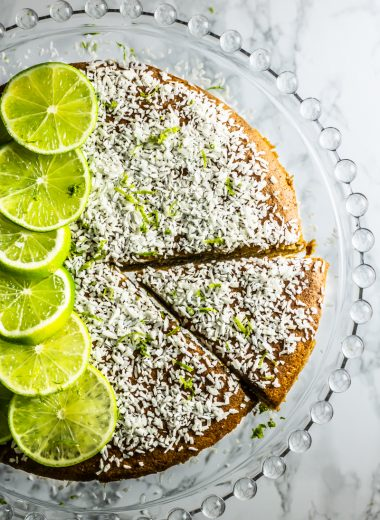 Very Coconutty and Lime Naked Cake on a glass cake stand shot from above with one piece taken out