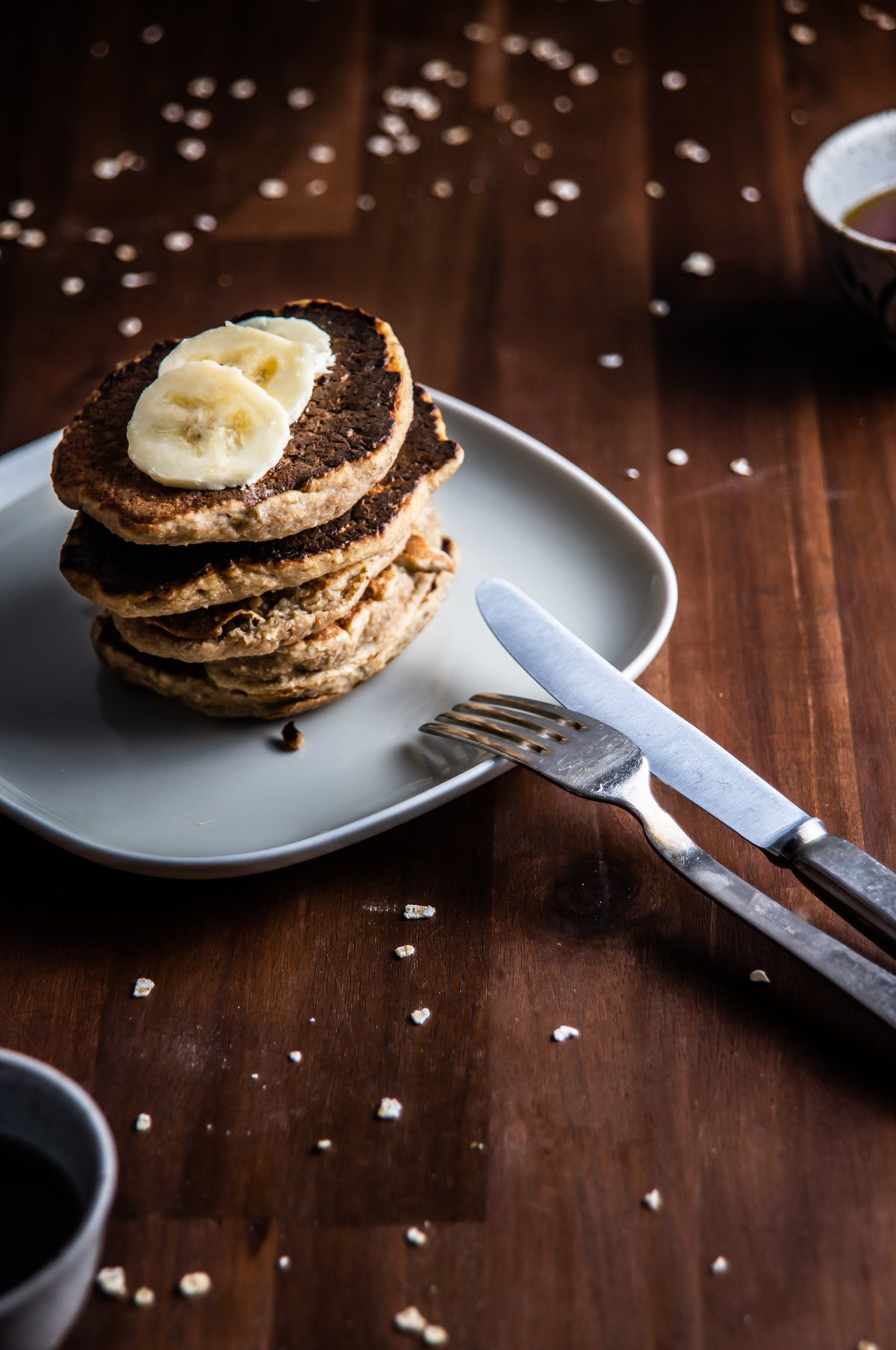 Stacked Easy Pantry Staple Pancakes with sliced bananas on top with cutlery on the side