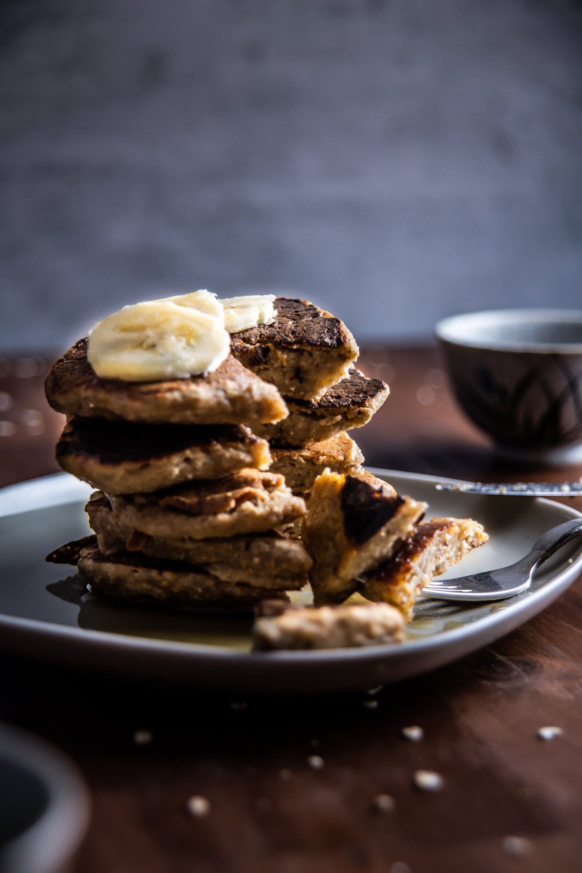 Stacked Easy Pantry Staple Pancakes with sliced bananas cut into and taken a chunk out of it