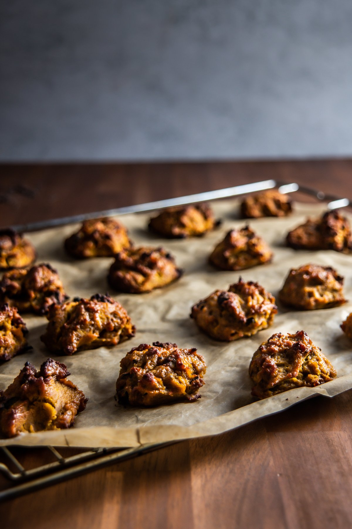 Chewy Pumpkin Spice Chocolate Chip Cookies on a baking tray with parchment paper
