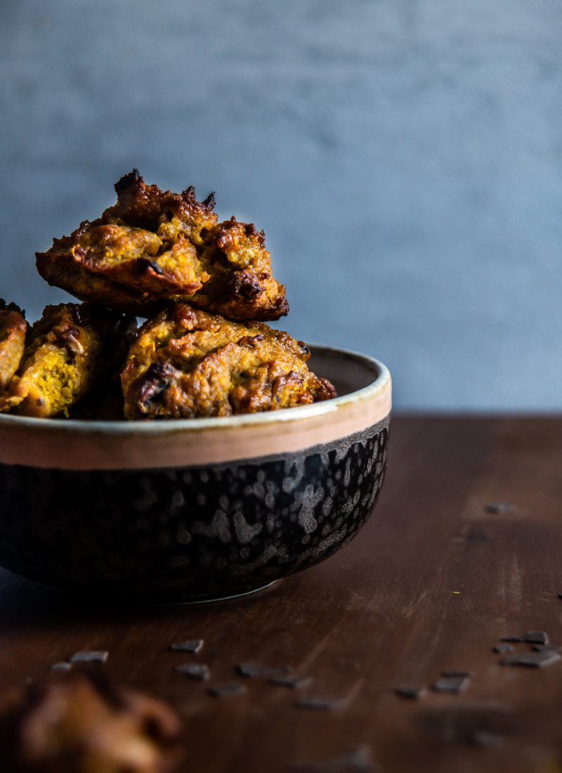 Chewy Pumpkin Spice Chocolate Chip Cookies in a bowl on a wooden board with grey background