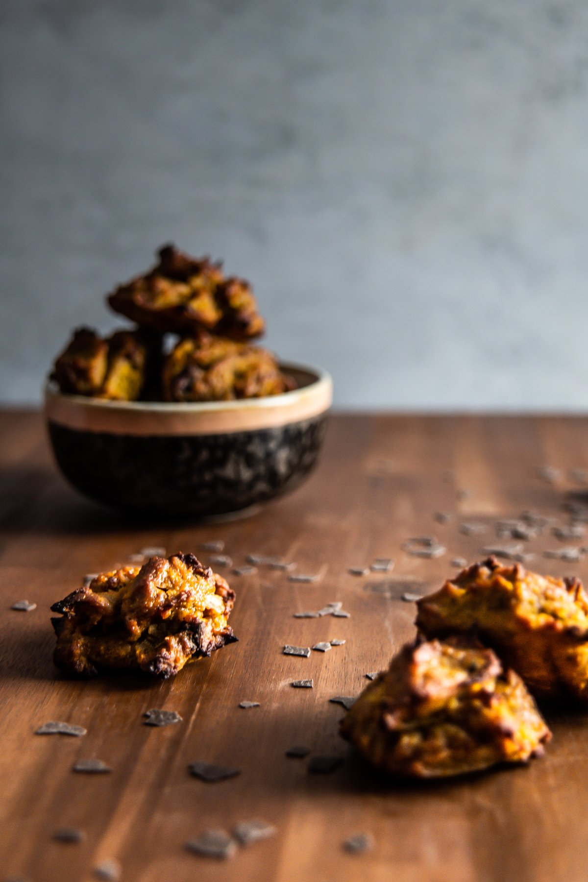 Chewy Pumpkin Spice Chocolate Cookies strewn on a wooden board with some cookies stacked in a bowl in the background