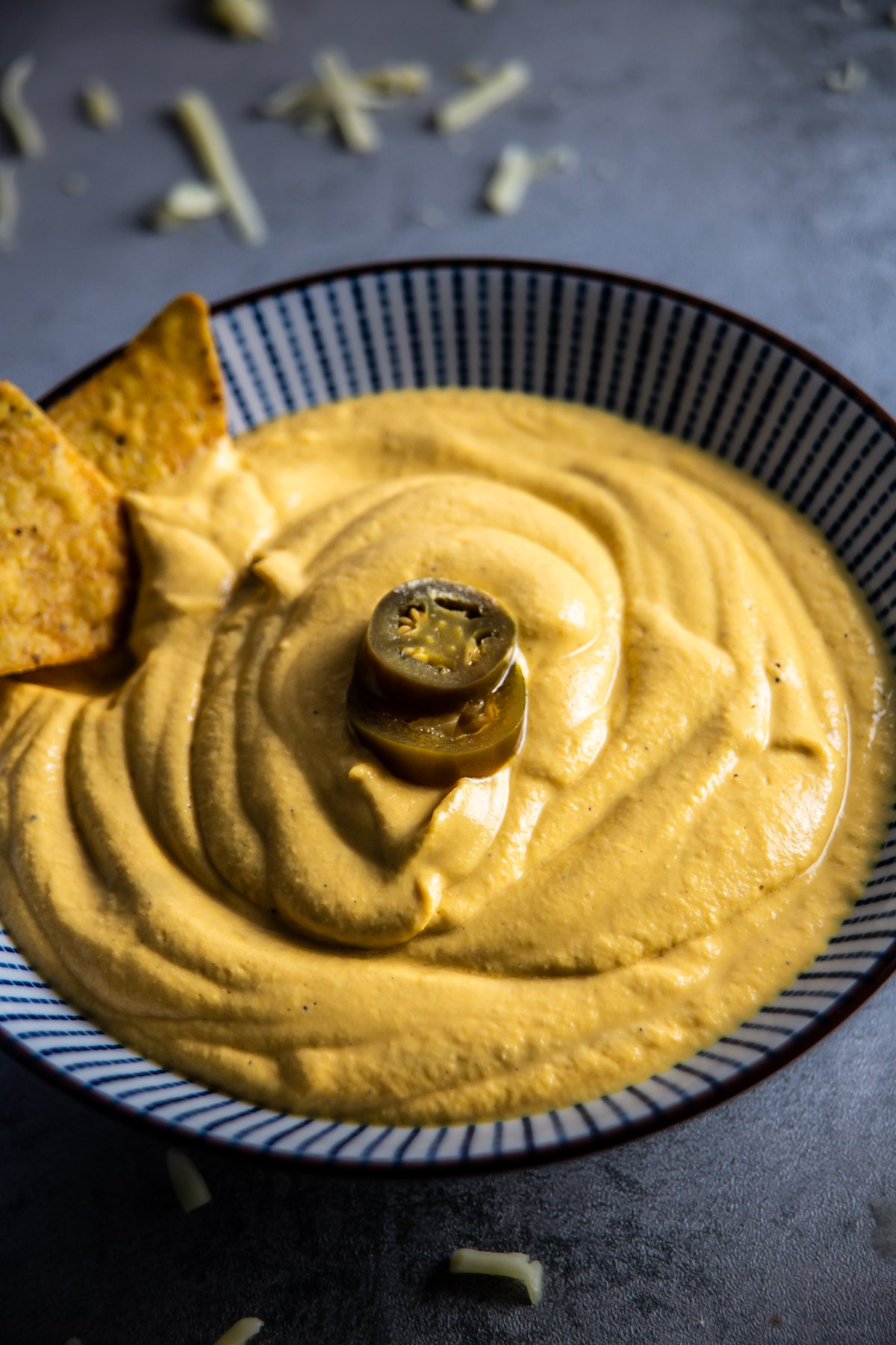 Vegan Cheese Sauce in a bowl on a grey background with nachos, jalapenos, and cheese strewn around photographed up close