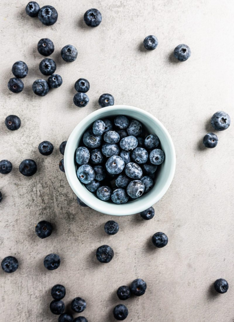 Blueberries in a blue bowl and strewn on a grey surface
