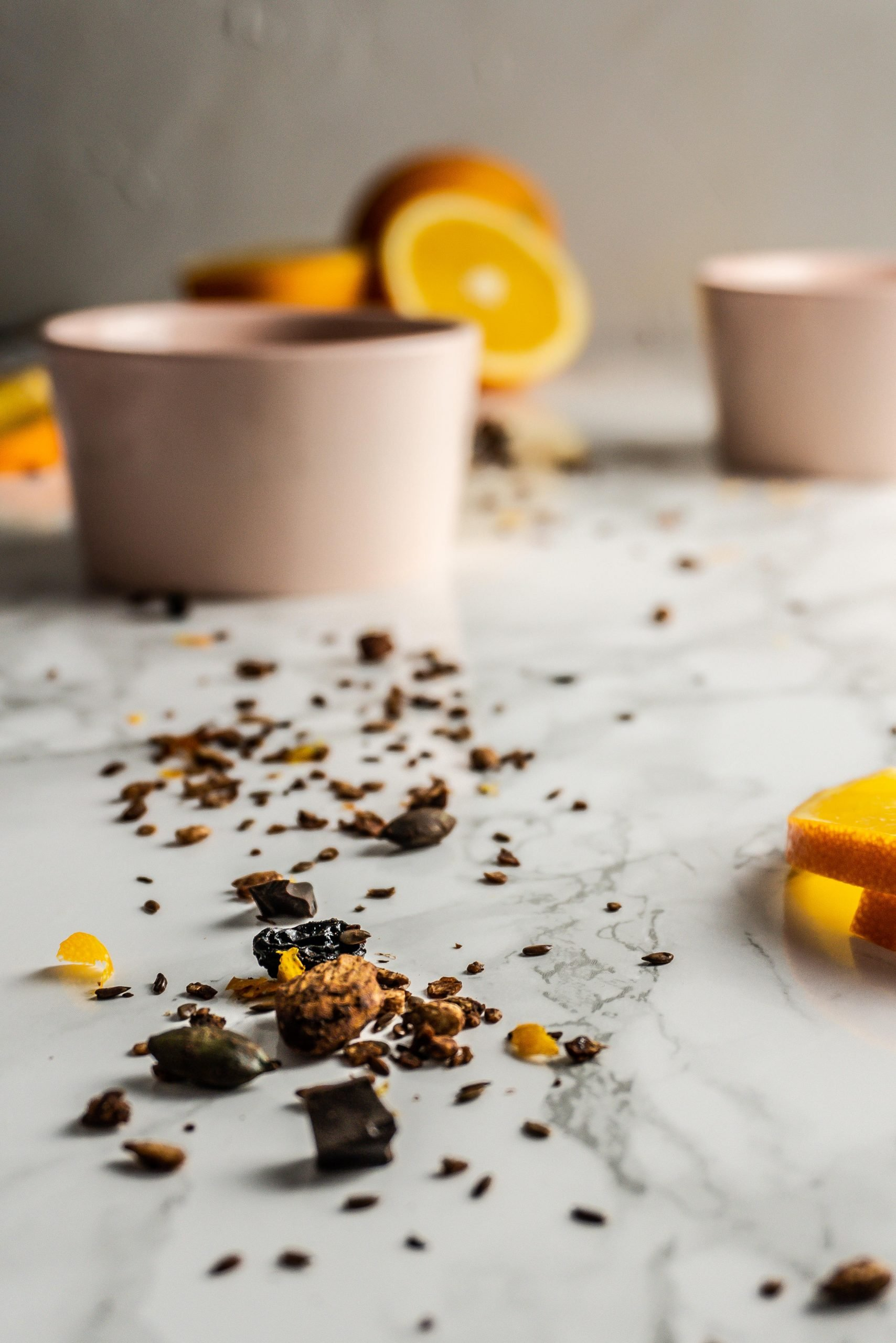 Chocolate Orange Granola strewn in focus with two bowls and oranges slightly visible in the background