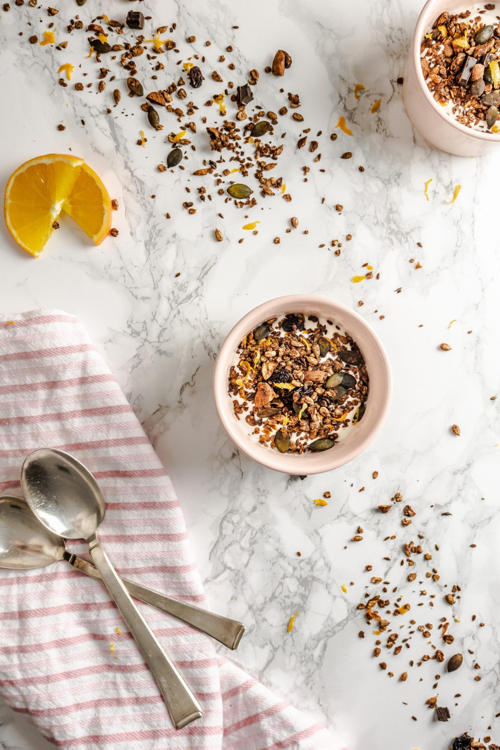 Chocolate Orange Granola strewn on a marble background and in two small bowls with yoghurt surrounded by spoons, a kitchen towel, and sliced oranges photographed from the top