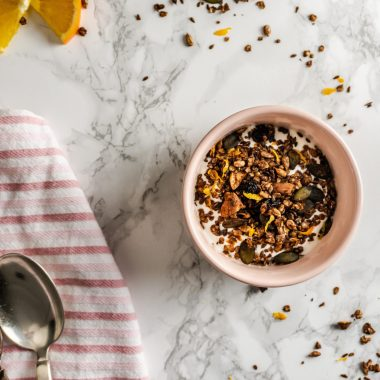 Chocolate Orange Granola strewn on a marble background and in a small bowl with yoghurt surrounded by spoons, a kitchen towel, and sliced oranges photographed from the top