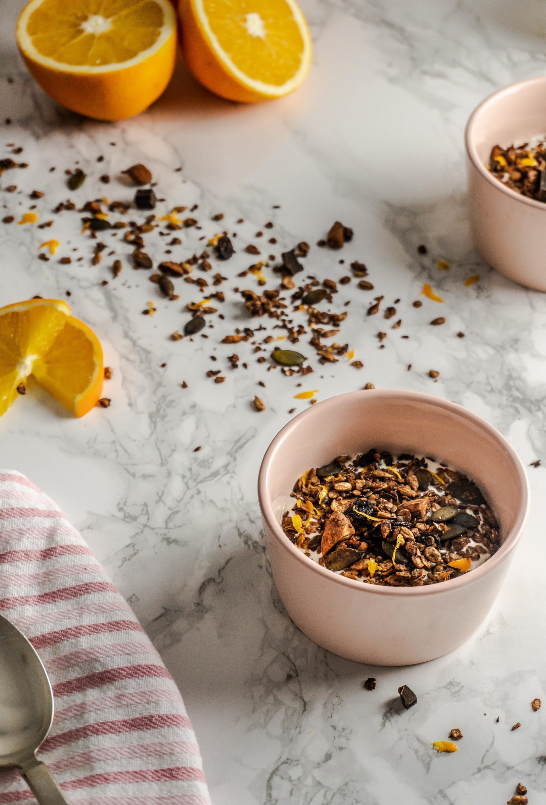 Chocolate Orange Granola strewn on a marble background and in small bowls with yoghurt surrounded by spoons, a kitchen towel, and sliced oranges photographed from a three-quarter angle