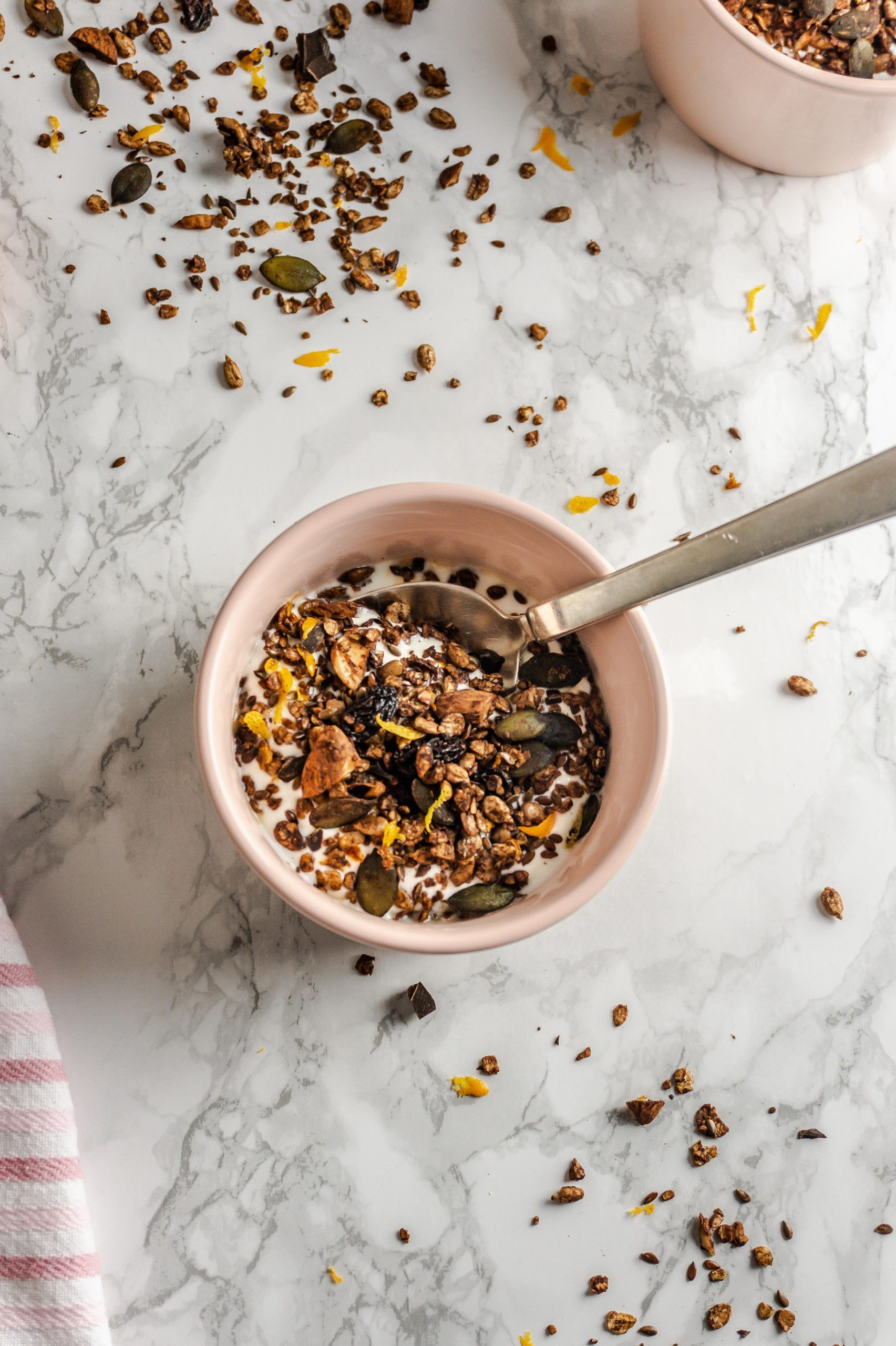 Chocolate Orange Granola in a small bowl with a spoon stuck in and some granola strewn around