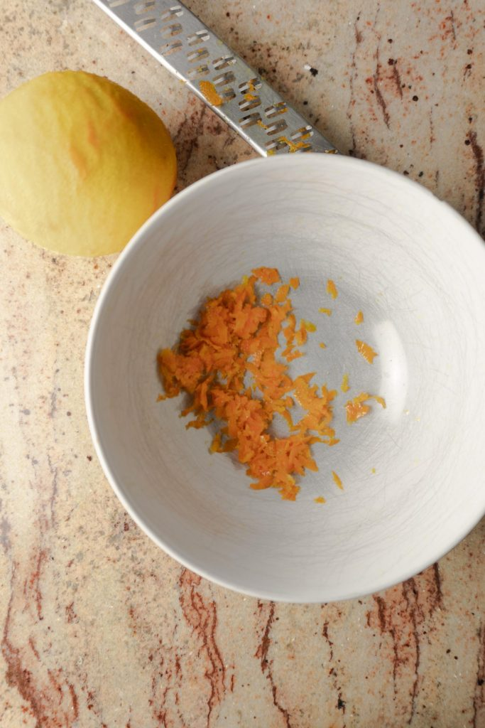Orange zest in a white bowl with a grater and an orange in background