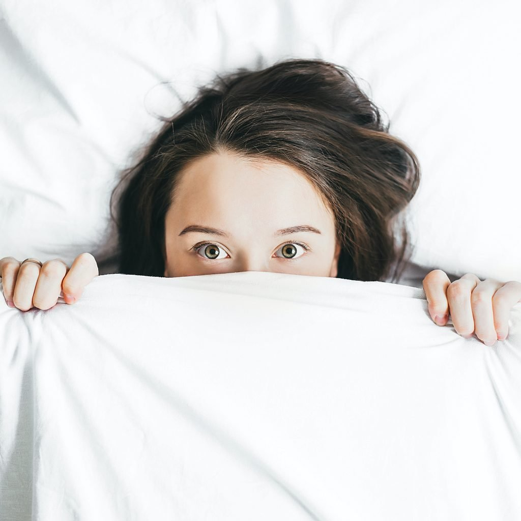 Female with long, brown hair, big open eyes and looking half way out of a blanket is trying how to establish a good sleeping routine