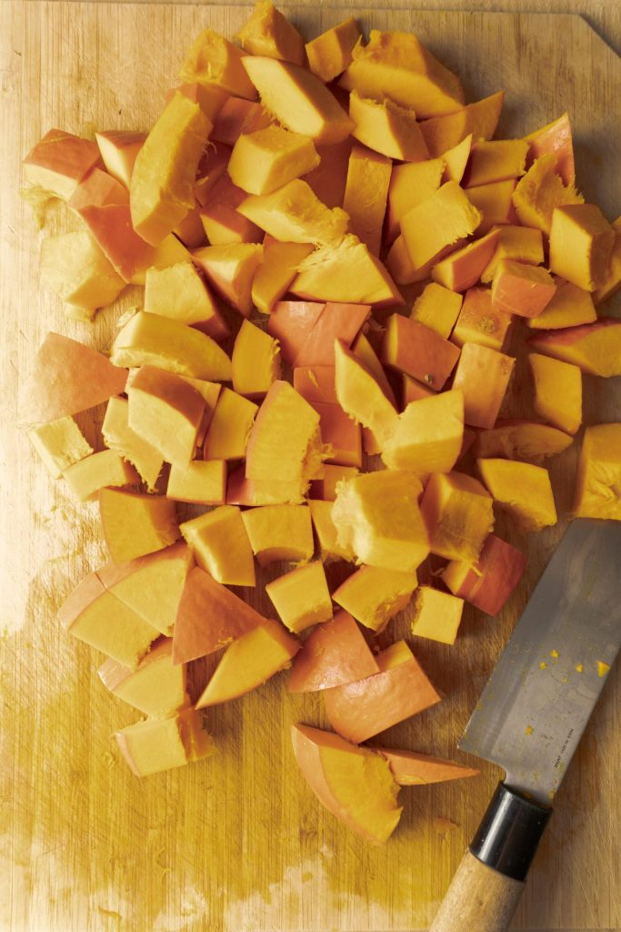 Cubed pumpkin on a chopping board with a