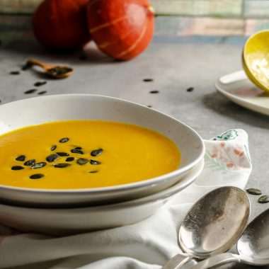 Red Thai Curry Pumpkin Soup in a soup bowl with a kitchen towel underneath and pumpkins, pumpkin seeds and a ladle visible in the background