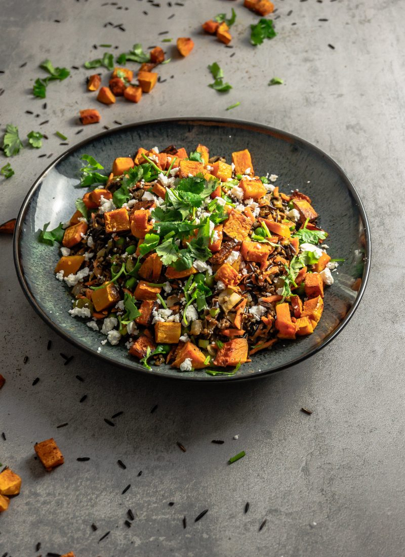 Wild Rice Salad with Roasted Butternut Squash photographed from a three quarter angle on a grey background with loads of wild rice, roasted butternut squash and cilantro strewn around