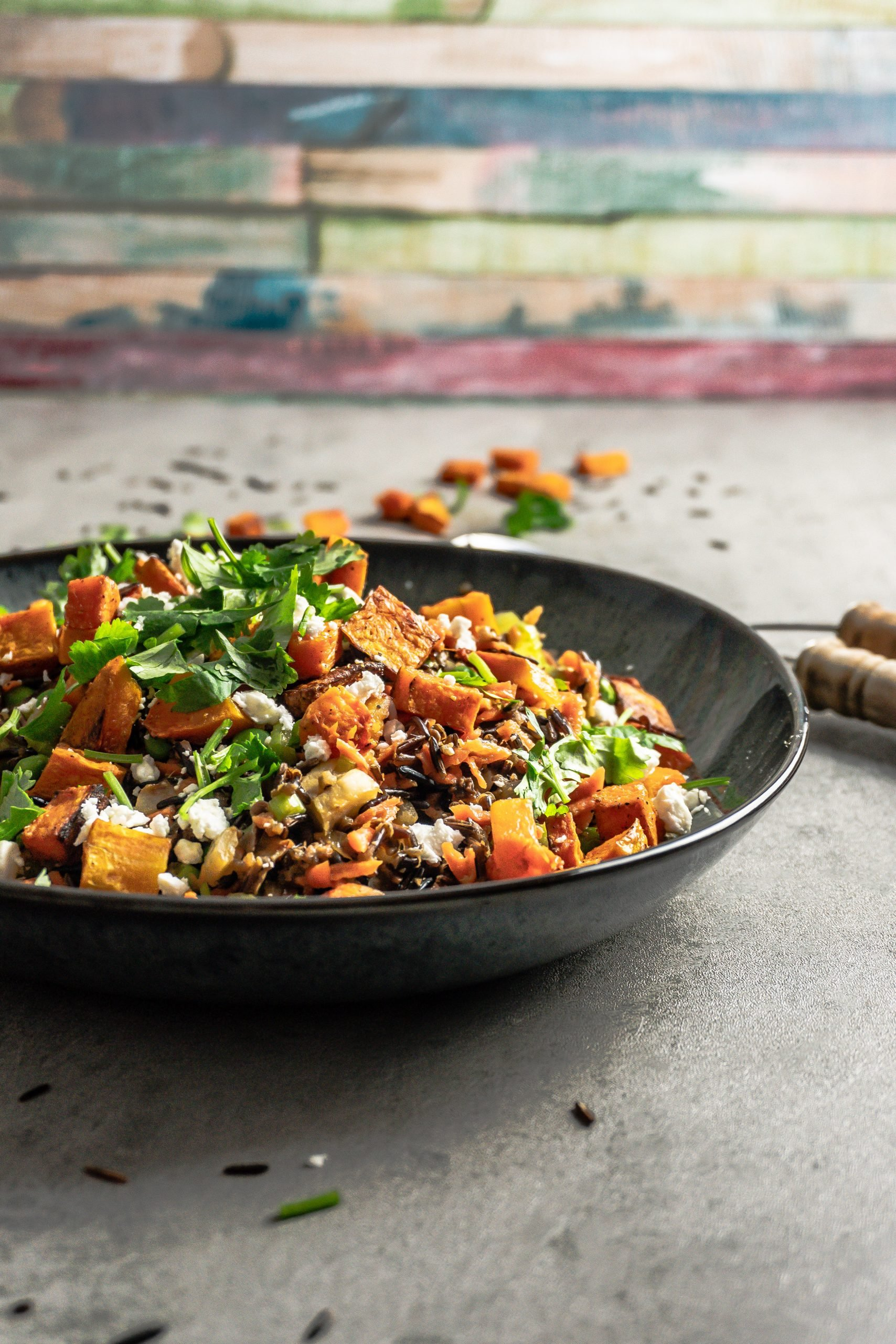 Wild Rice Salad with Roasted Butternut Squash on a plate with salad tongs in the background