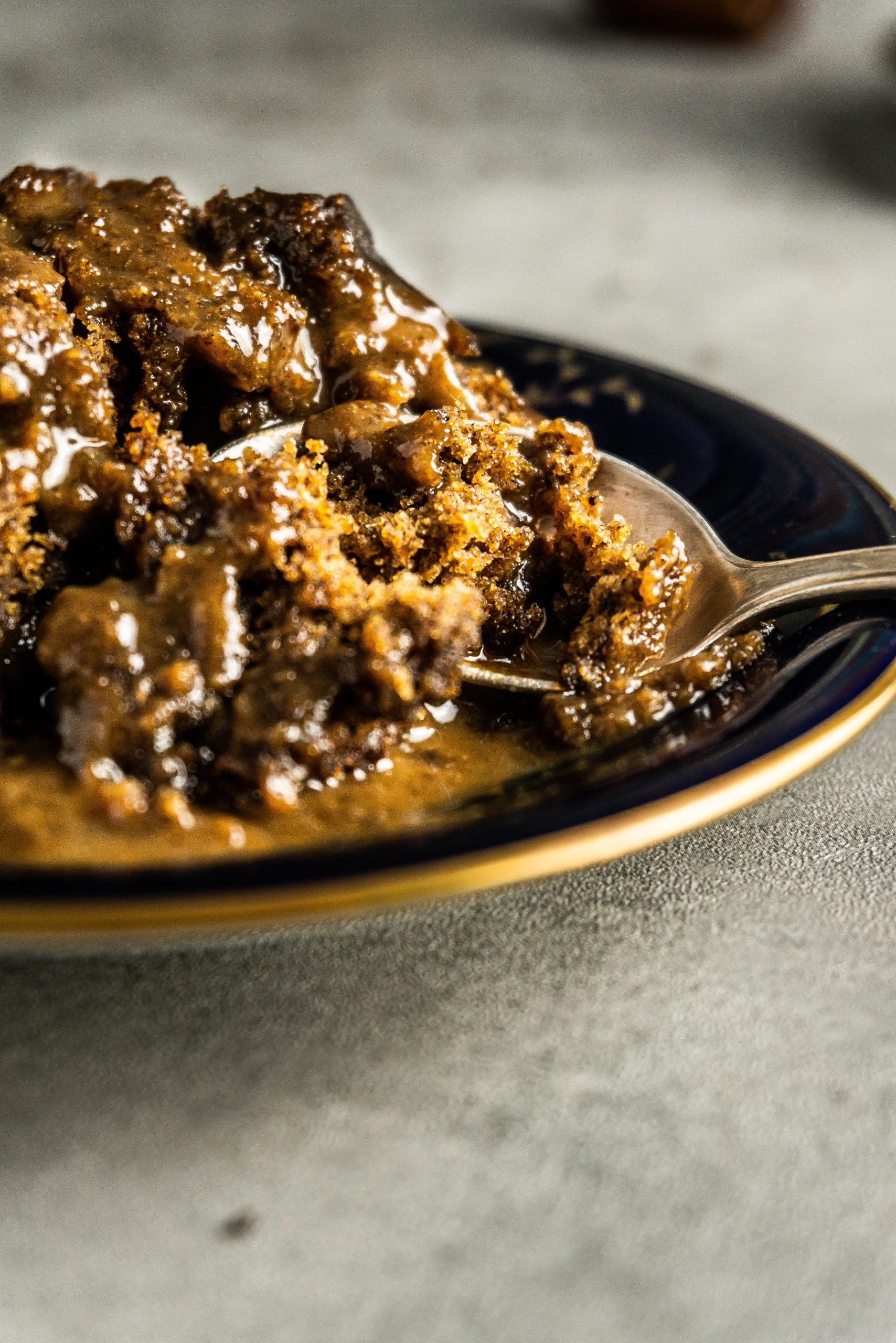Vegan Hot Sticky Toffee Pudding covered in sauce tugged in with a spoon photographed up close