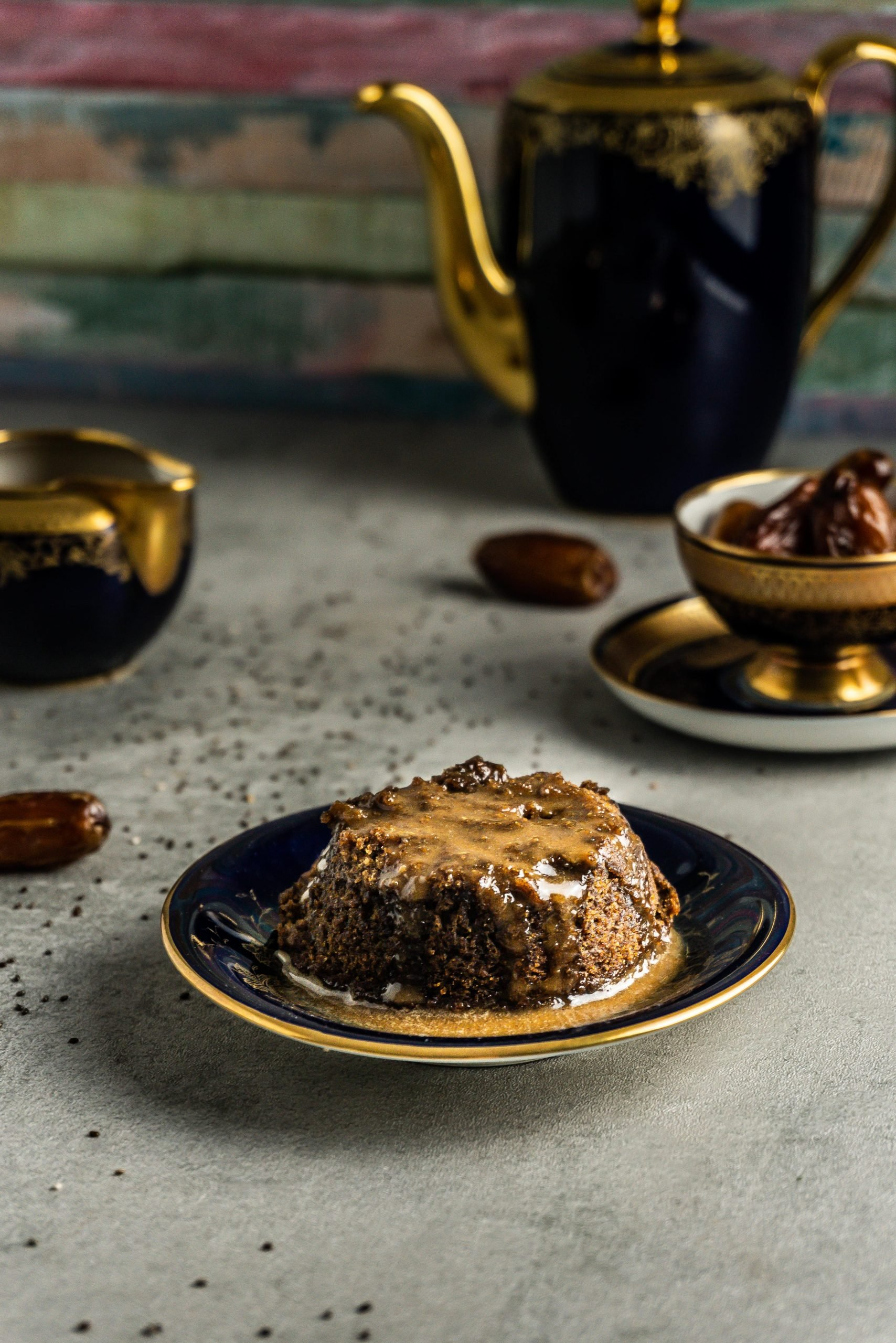 Vegan Hot Sticky Toffee Pudding on a small plate surrounded by dates, chia seeds, more sauce and a small cup filled with dates. Photographed from a three-quarter angle