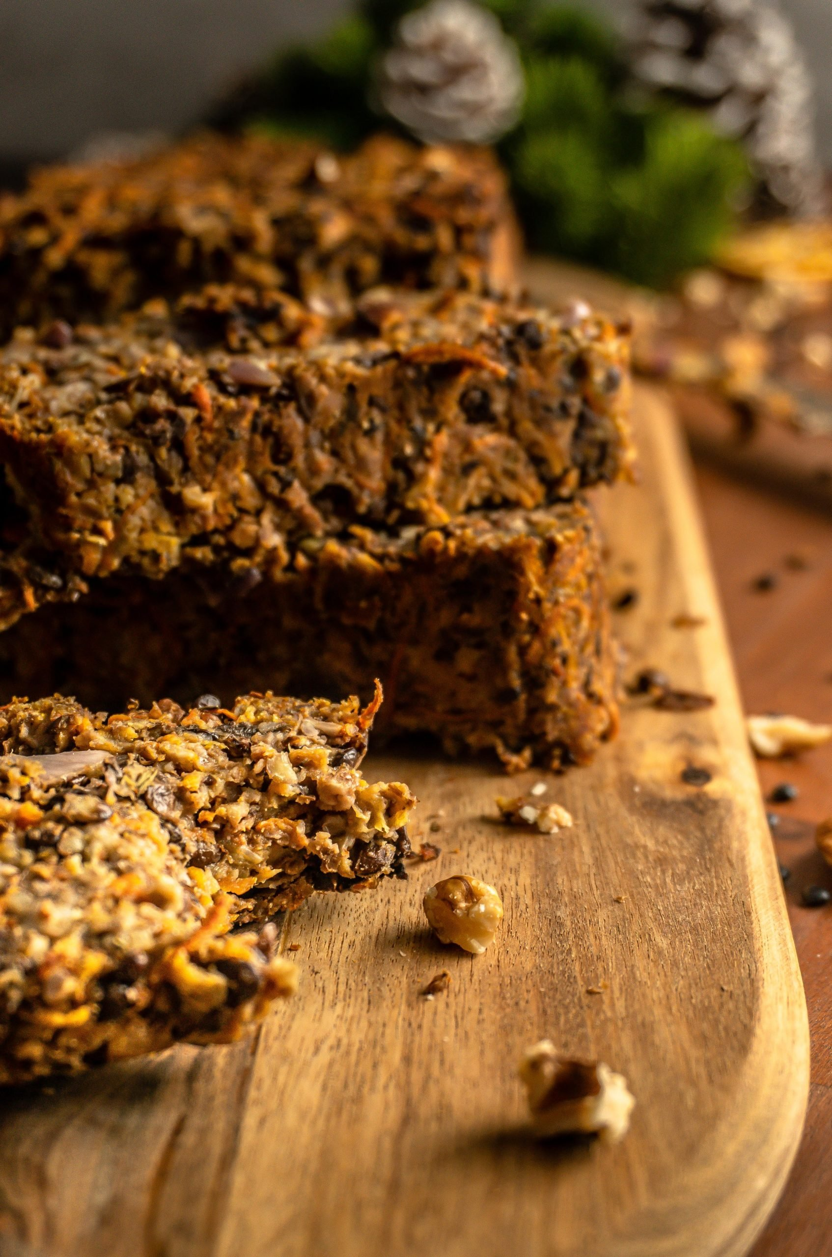 """Bitten into piece from the Lentil Mushroom Walnut """"Meat"""" Loaf with some further slices visible in the background. Shot from a side angle."""