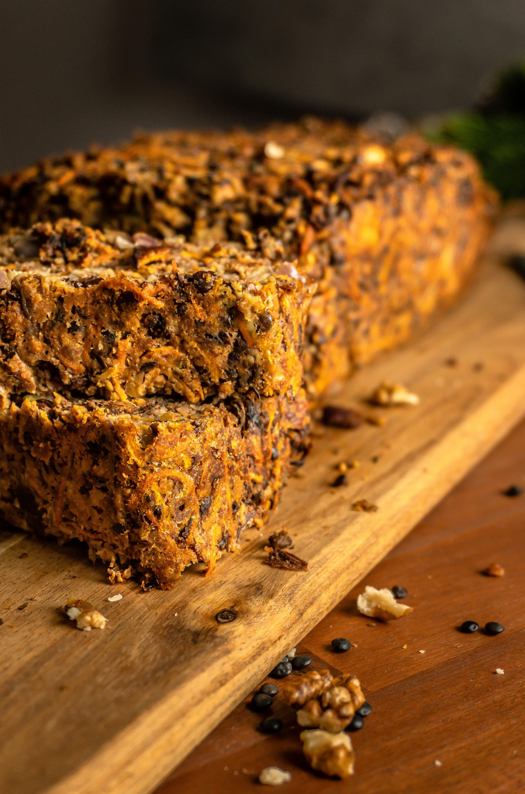 """Stacked pieces of Lentil Mushroom Walnut """"Meat"""" Loaf with the loaf visible in the background"""