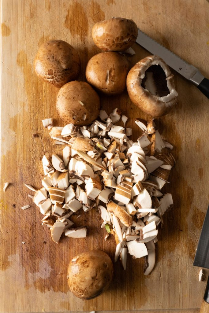 Chopped mushrooms on a wooden chopping board