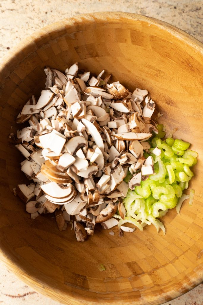 Chopped celery and mushrooms in a wooden salad bowl
