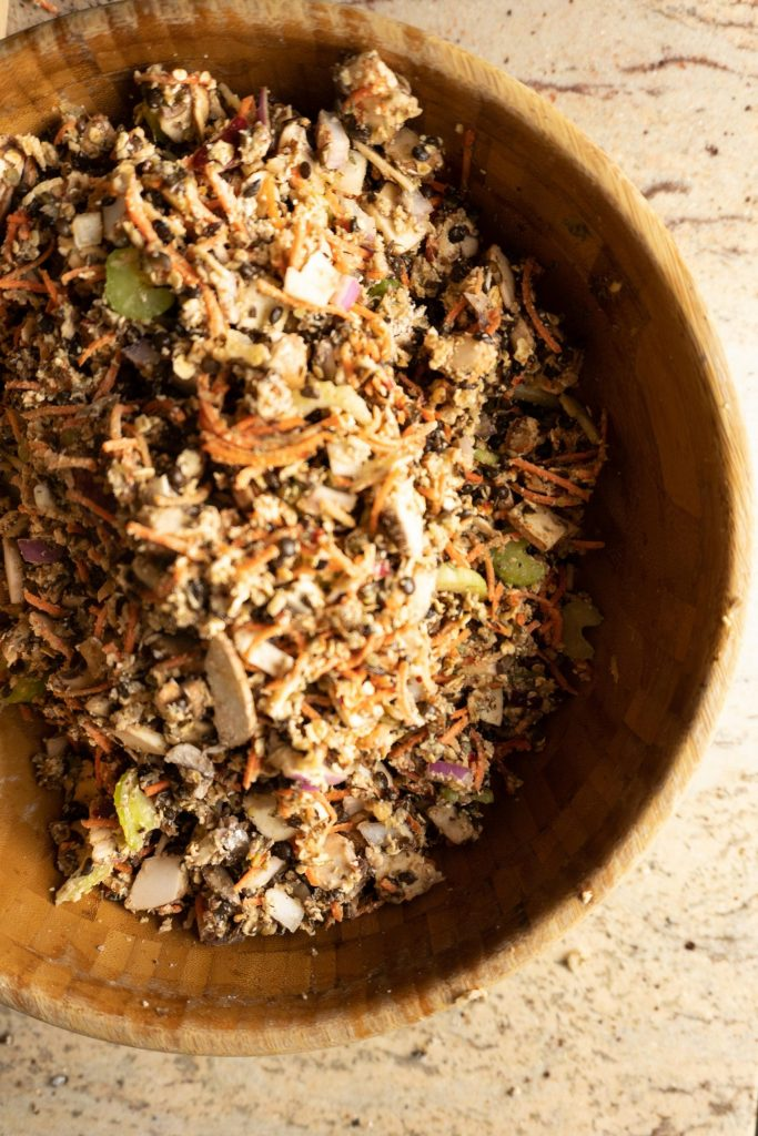 """All ingredients for the Lentil Mushroom Walnut """"Meat"""" Loaf mixed through in a wooden salad bowl"""
