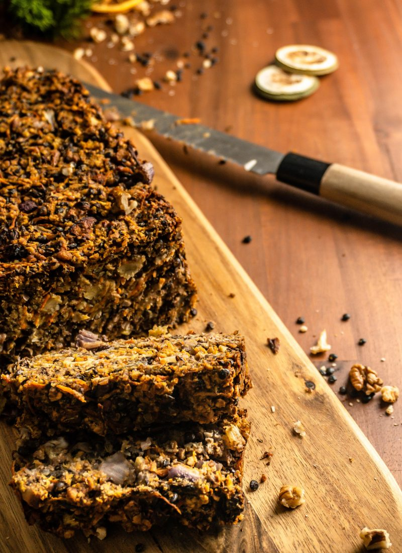"""Lentil Mushroom Walnut """"Meat"""" Loaf cut into pieces on a chopping board with a knife in the background. Shot from above."""