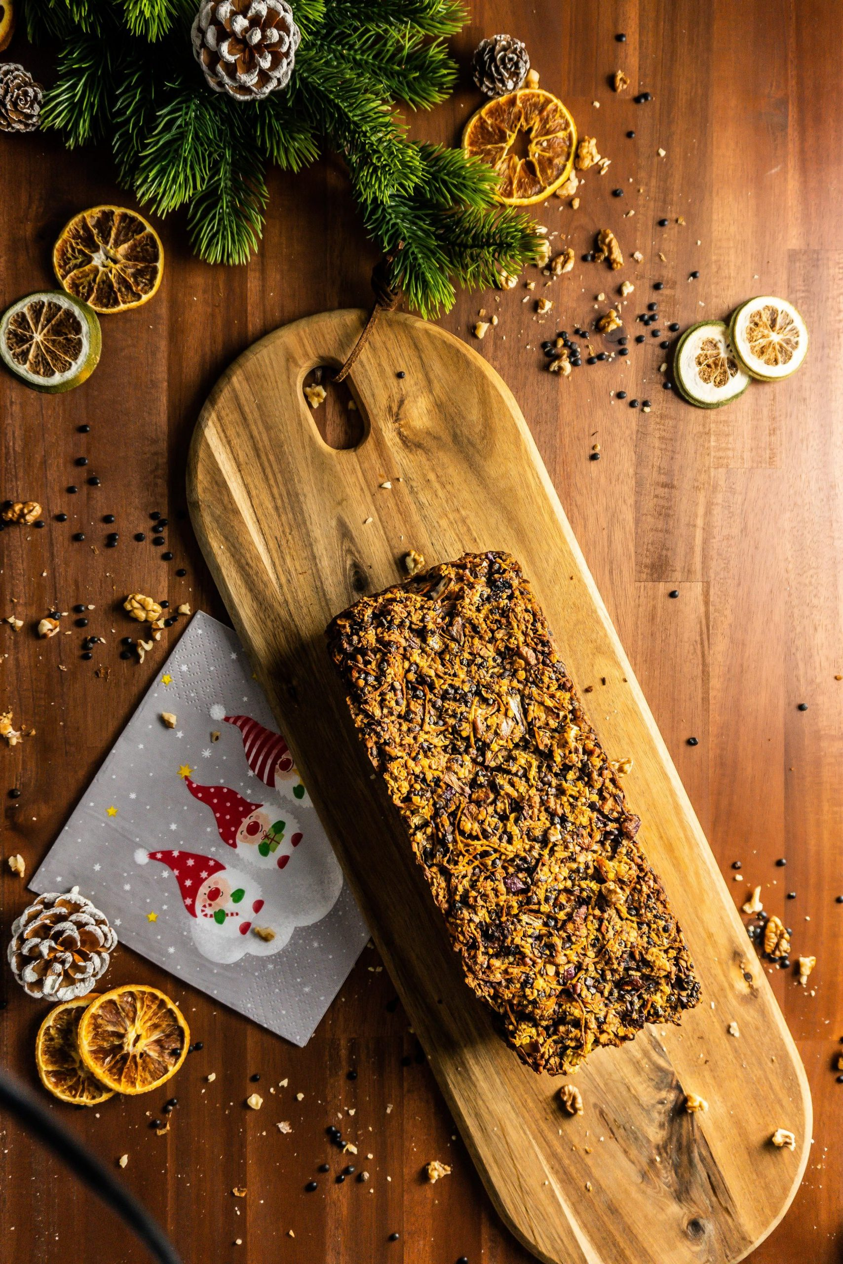 """Lentil Mushroom Walnut """"Meat"""" Loaf on a cutting board surrounded by Christmas napkins, dried orange slices, and lentil and walnut pieces"""