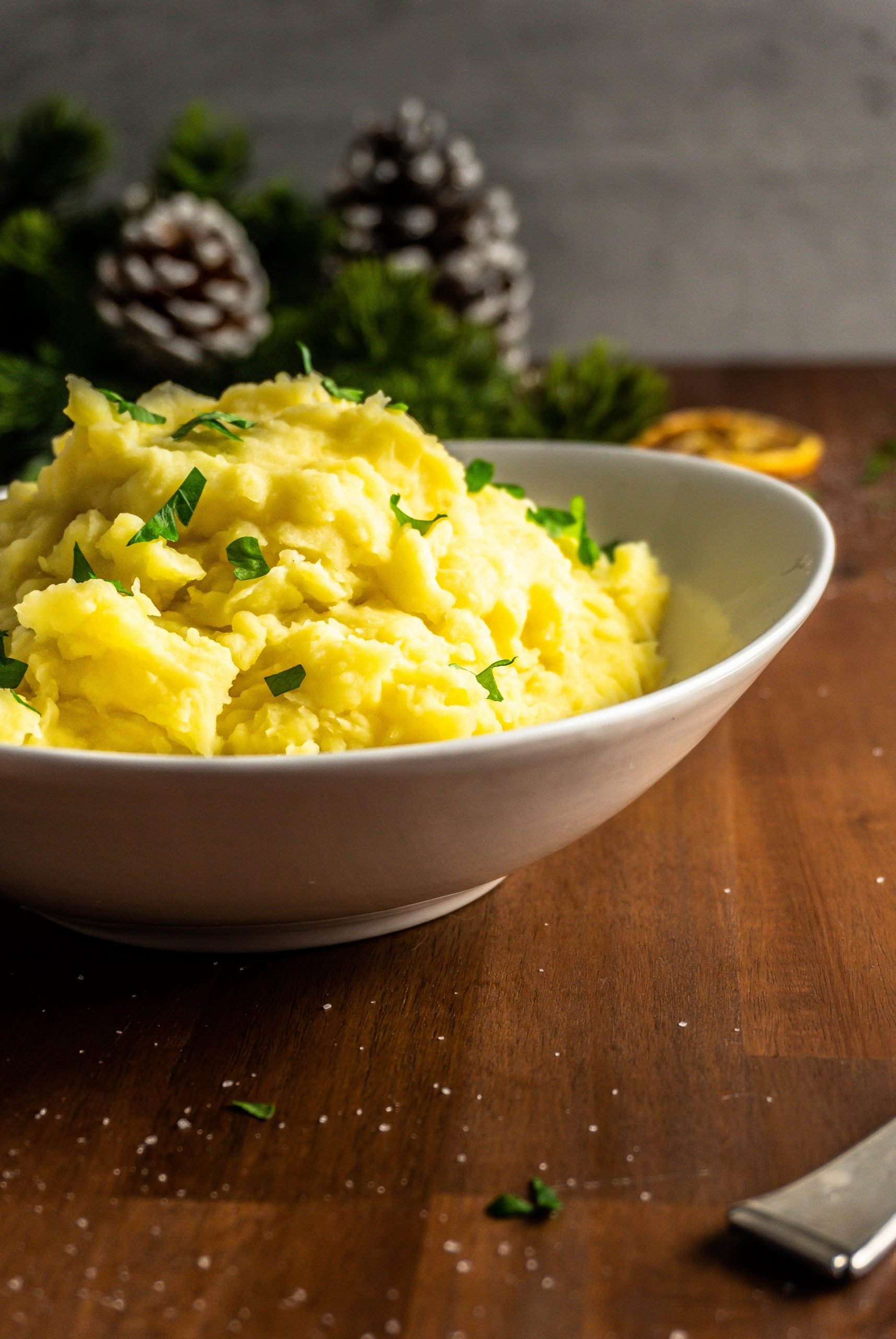 Creamy Mashed Potatoes photographed in a bowl with parsley strewn on top. Shot from a three-quarter angle.