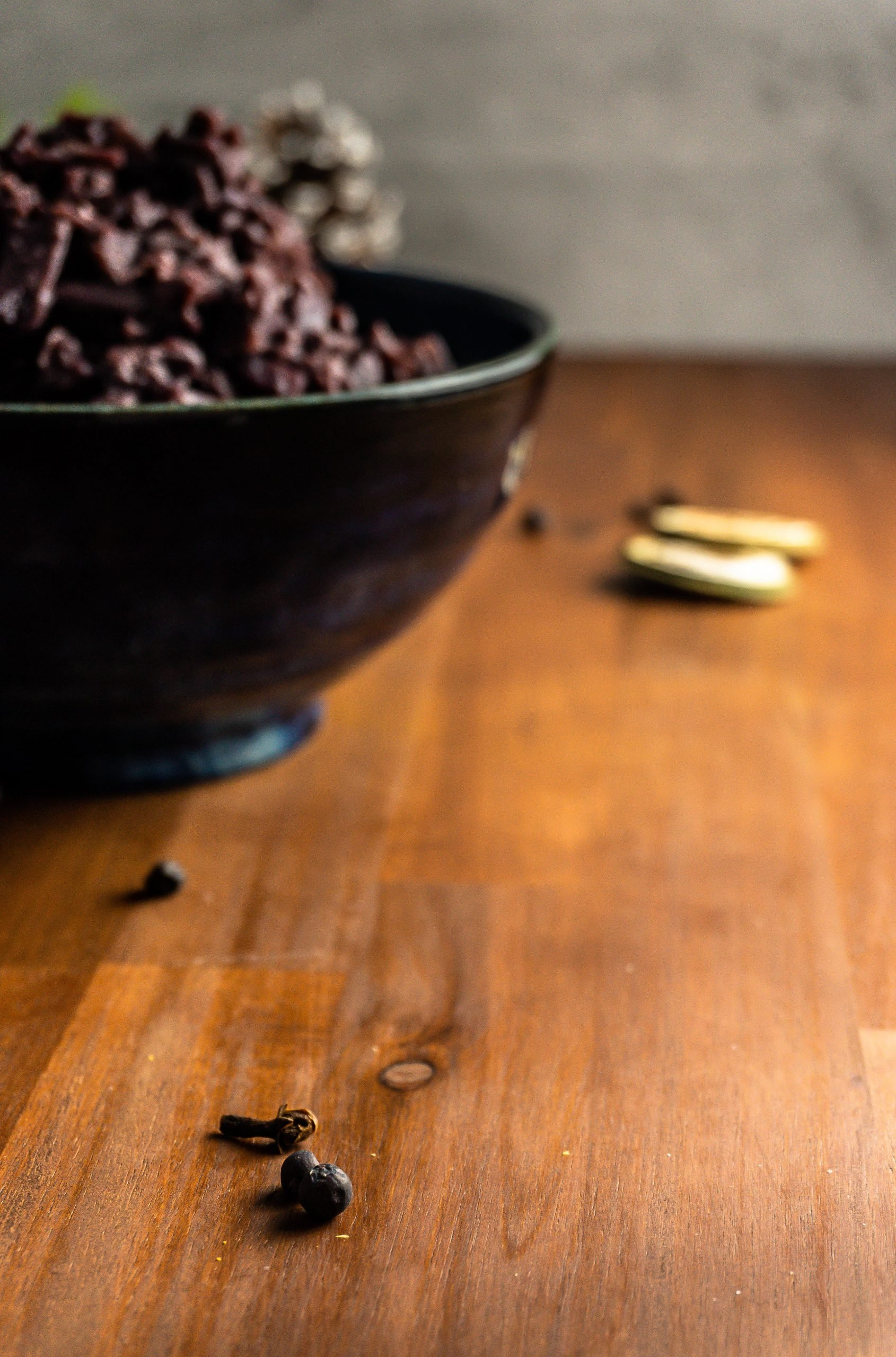 Clove and juniper berries on a wooden underground with German Red Cabbage (Rotkohl) visible in the background