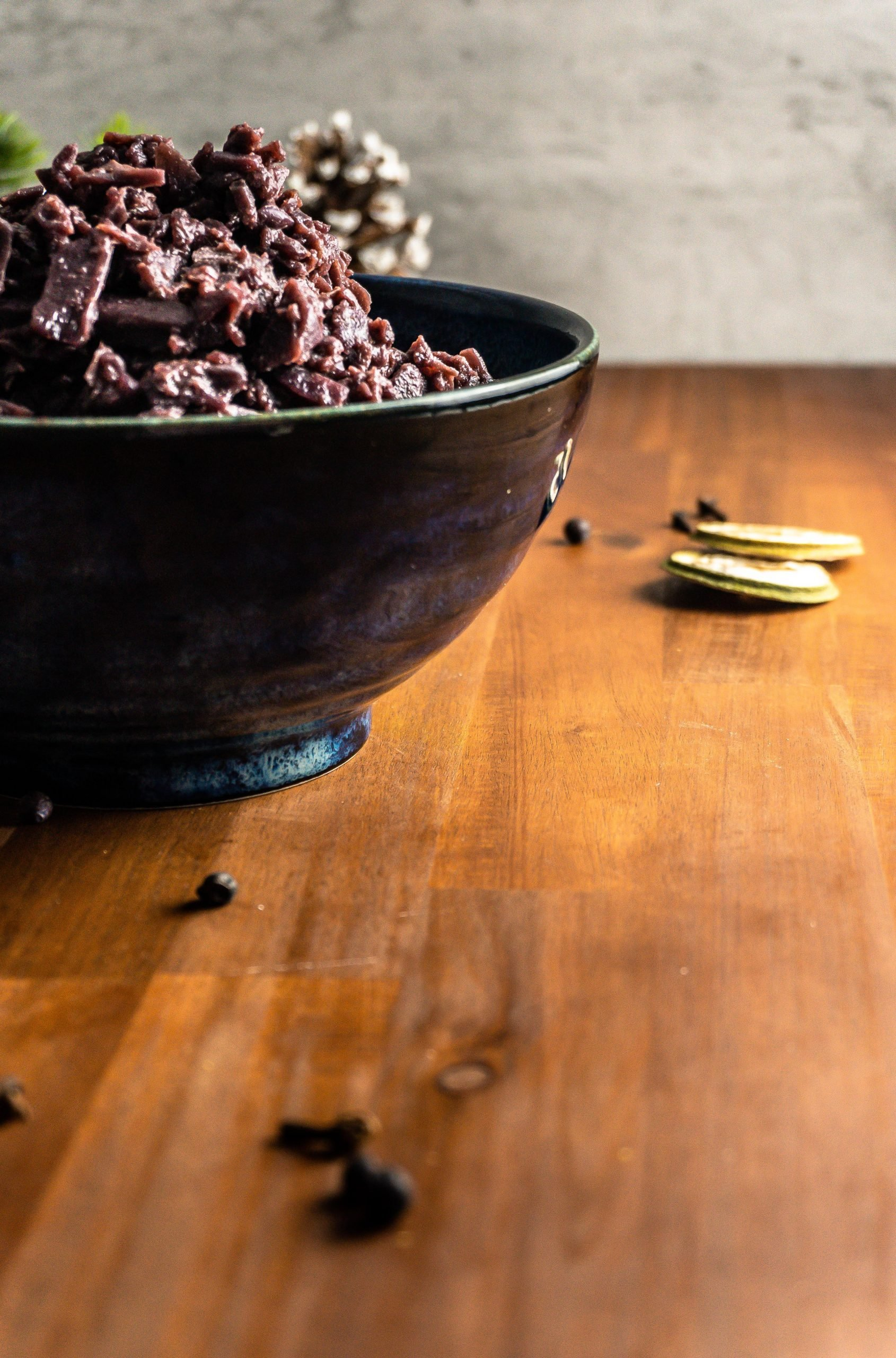 Clove and juniper berries blurred in the fron with German Red Cabbage (Rotkohl) visible in the background