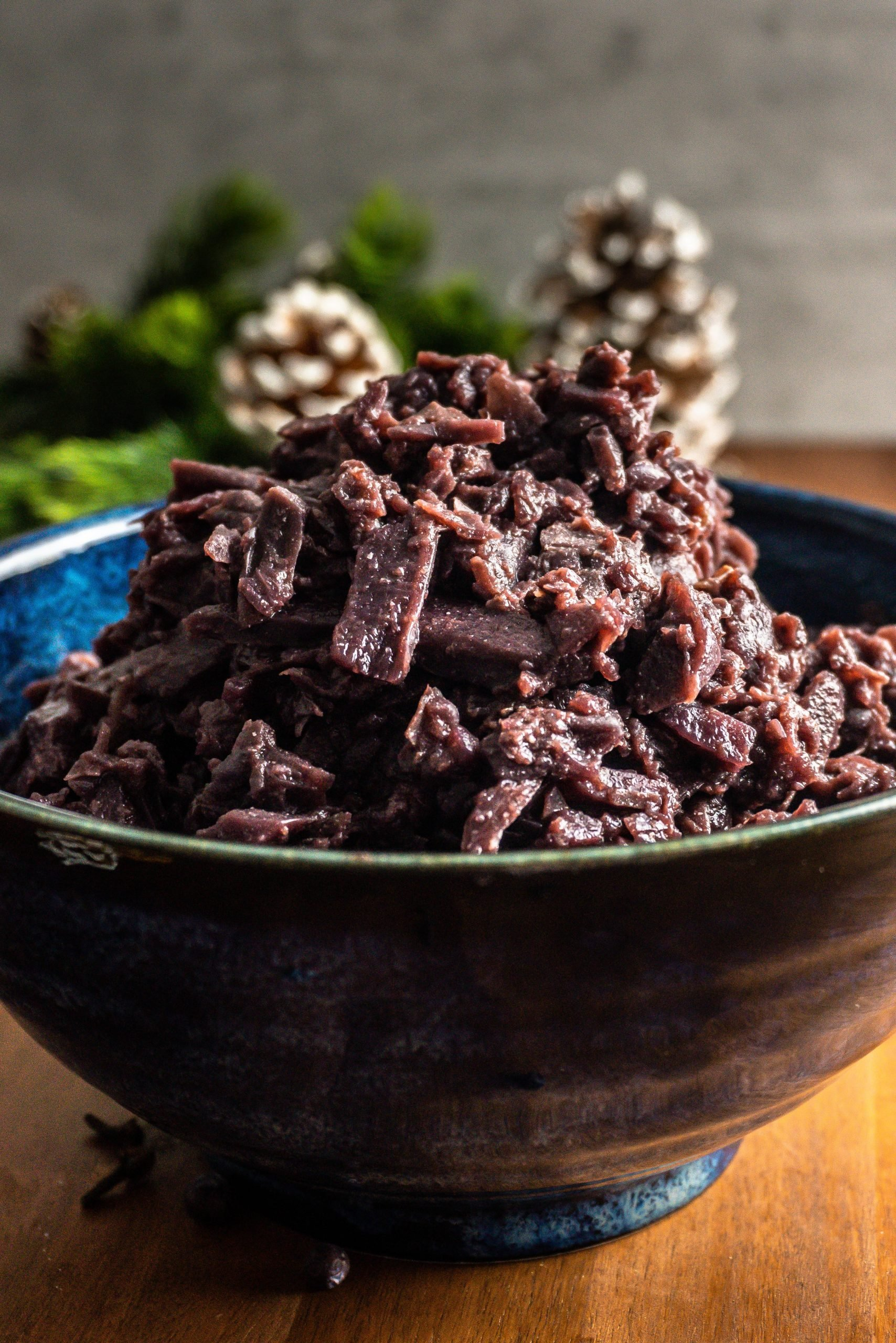 German Red Cabbage (Rotkohl) in a blue bowl on a dark wooden background with dried sliced orange slices, pine cones, cloves, and juniper berries as decoration. Shot up close with the red cabbage in focus