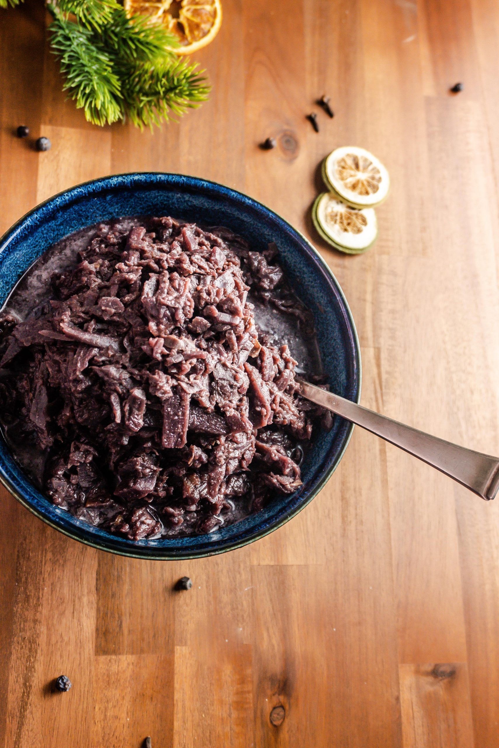 German Red Cabbage (Rotkohl) in a blue bowl with a spoon on a dark wooden background with dried sliced orange slices, pine cones, cloves, and juniper berries as decoration