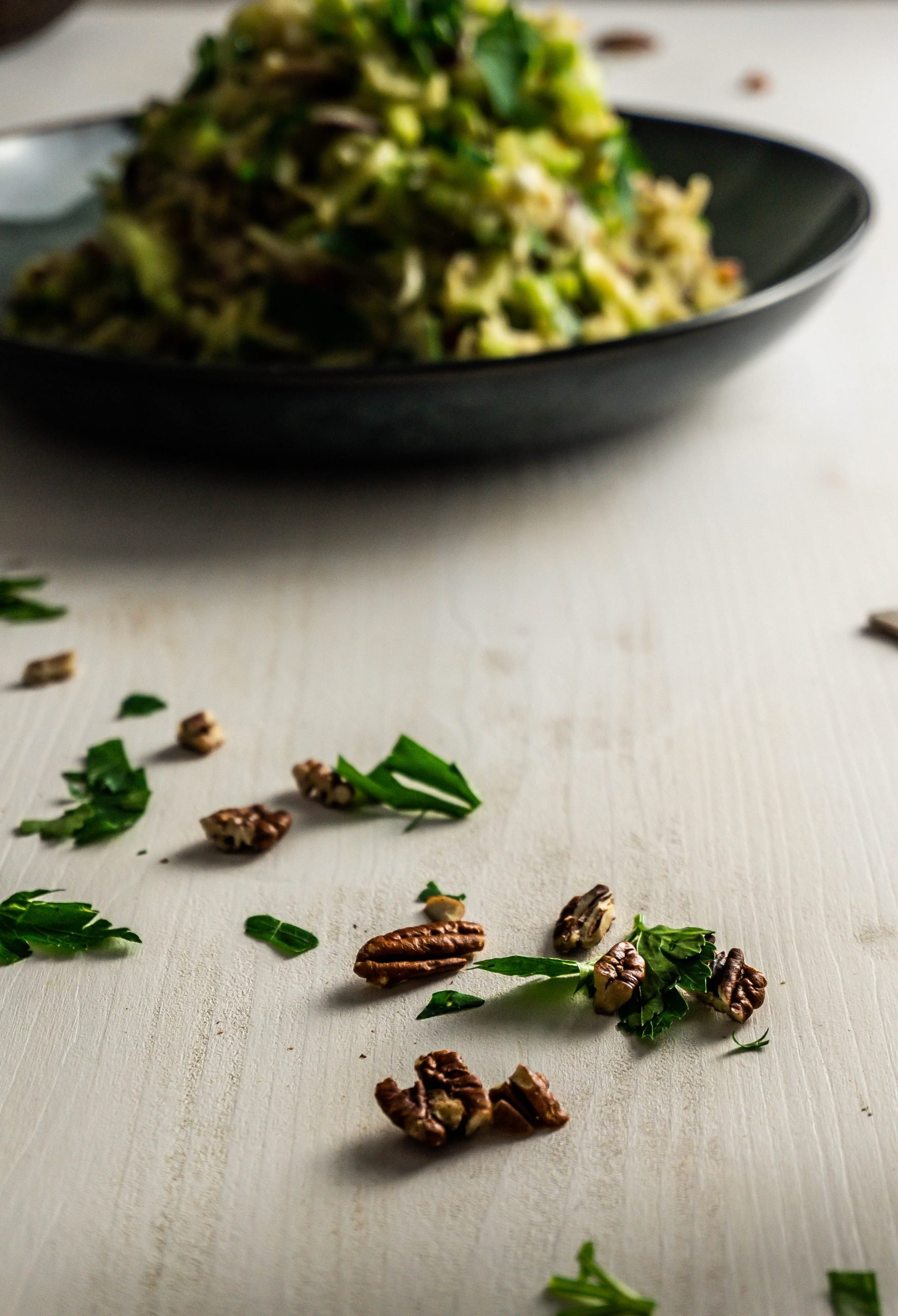 Chopped parsley and pecan nuts on a white surface with my mother-in-law's apple celery salad visible in the background