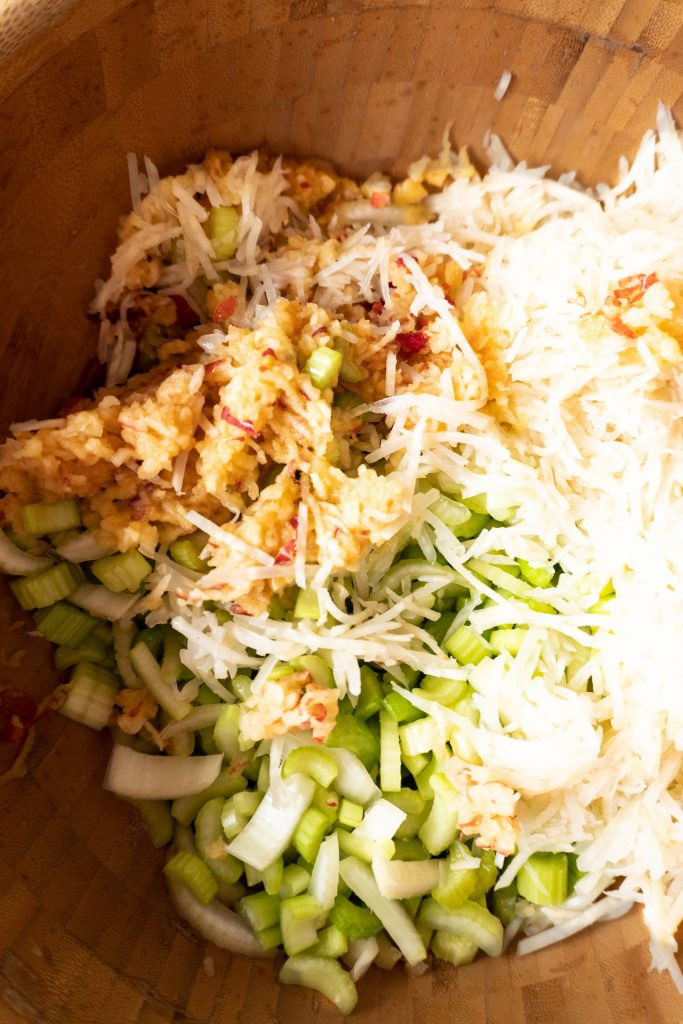 Chopped celery, pickled celery, and grated apple in a wooden bowl